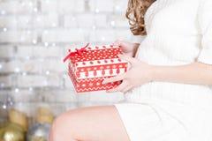 Femme enceinte de jeunes tournée en longueur et prises Noël prese image stock