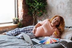 Femme enceinte de plein terme détendant sur le lit photos stock
