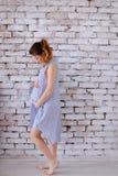 Femme enceinte de Si-ngan d'Européen de cauca portant la robe bleue se tenant à l'arrière-plan de mur de briques et tenant le ven photographie stock libre de droits