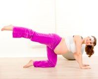 Femme enceinte de sourire faisant l'exercice d'aérobic Image stock