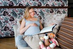 Femme enceinte de sourire se reposant sur le sofa avec les jouets du ` s d'enfant et le livre de lecture image stock