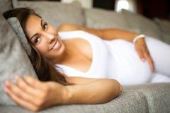 Femme enceinte de sourire se trouvant sur le sofa avec sa main au ventre image libre de droits