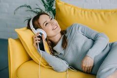 femme enceinte de sourire se trouvant sur le sofa et écoutant la musique Photographie stock