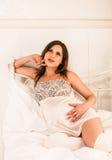 Femme enceinte de sourire tenant son ventre Image stock
