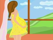 Femme enceinte devant l'hublot Image libre de droits