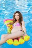 Femme enceinte détendant près de la piscine Photographie stock libre de droits