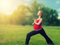 Femme enceinte en bonne santé faisant le yoga en nature Photos libres de droits