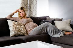 Femme enceinte en bonne santé se trouvant sur un divan Image libre de droits