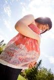 Femme enceinte en parc regardant le ventre Photographie stock libre de droits