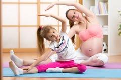 Femme enceinte et enfant mignons à la forme physique de gymnase Image libre de droits