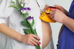 Femme enceinte et homme avec des chaussettes de bébé images stock