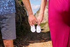 Femme enceinte et homme tenant des chaussures de bébé dans des mains La futurs maman et papa, parents tient de petites chaussures Photo libre de droits