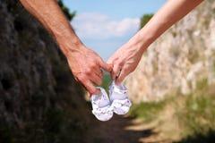 Femme enceinte et homme tenant des chaussures de bébé dans des mains La futurs maman et papa, parents tient de petites chaussures Image stock