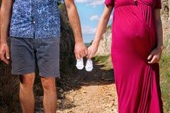 Femme enceinte et homme tenant des chaussures de bébé dans des mains La futurs maman et papa, parents tient de petites chaussures Photos stock