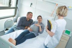 Femme enceinte et mari ayant la visite de docteur photos libres de droits