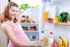 Femme enceinte et réfrigérateur avec la nourriture biologique photo libre de droits