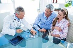 Femme enceinte et son mari discutant avec le docteur Photos libres de droits