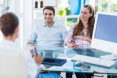 Femme enceinte et son mari discutant avec le docteur Images libres de droits