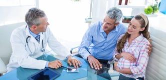 Femme enceinte et son mari discutant avec le docteur Image libre de droits