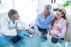 Femme enceinte et son mari discutant avec le docteur Photo libre de droits