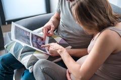 Femme enceinte et son mari observant la photo de rayon X de l'enfant Images stock