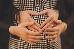 Femme enceinte et son mari tenant ses mains dans un shap de coeur Photographie stock