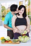 Femme enceinte faisant cuire avec son mari Image libre de droits