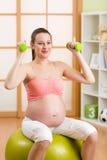 Femme enceinte faisant des exercices de forme physique se reposant dessus photos libres de droits