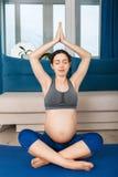 Femme enceinte faisant l'exercice de yoga Photos stock