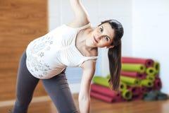 Femme enceinte faisant l'exercice de yoga, inclinant sa tête dans le côté, regardant l'appareil-photo image libre de droits