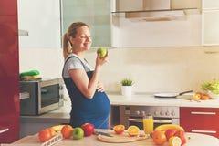 femme enceinte faisant le jus de fruit sain et mangeant la pomme Images stock