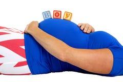 Femme enceinte fixant avec les blocs en bois orthographiant le garçon sur elle Photos stock