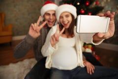Femme enceinte gaie de sourire avec son mari célébrant Noël tout en se reposant ensemble sur un plancher et prenant un selfie à l Photo stock