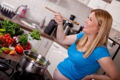 Femme enceinte goûtant le potage aux légumes sain Image stock