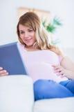 Femme enceinte heureuse à l'aide du comprimé Image libre de droits