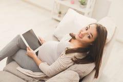 Femme enceinte heureuse à l'aide du comprimé numérique à la maison Photos stock