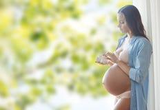 Femme enceinte heureuse avec des butins de bébé à la maison Photographie stock
