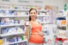 Femme enceinte heureuse avec le médicament à la pharmacie Images libres de droits