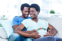 Femme enceinte heureuse avec le mari touchant son ventre Photographie stock libre de droits