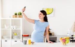 Femme enceinte heureuse avec le smartphone à la cuisine Photos stock