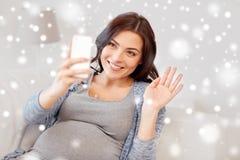 Femme enceinte heureuse avec le smartphone à la maison photo libre de droits