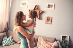 Femme enceinte heureuse avec sa fille d'enfant en bas âge à la maison Image libre de droits