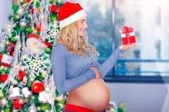 Femme enceinte heureuse dans le réveillon de Noël Image stock