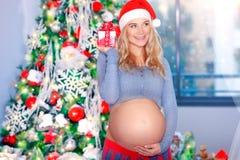 Femme enceinte heureuse dans le réveillon de Noël Photos libres de droits