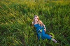 Femme enceinte heureuse de sourire se trouvant sur l'herbe Photographie stock