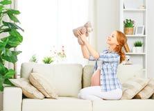 Femme enceinte heureuse détendant à la maison avec l'ours de nounours de jouet Photographie stock libre de droits