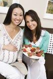 Femme enceinte heureuse et ami ayant la nourriture Photographie stock libre de droits