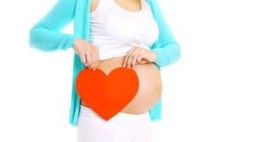 Femme enceinte heureuse et grand coeur rouge dans des mains Photo stock