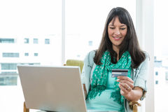 Femme enceinte heureuse faisant des emplettes en ligne sur son ordinateur portable Images libres de droits