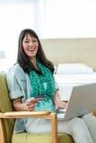 Femme enceinte heureuse faisant des emplettes en ligne sur son ordinateur portable Photos libres de droits